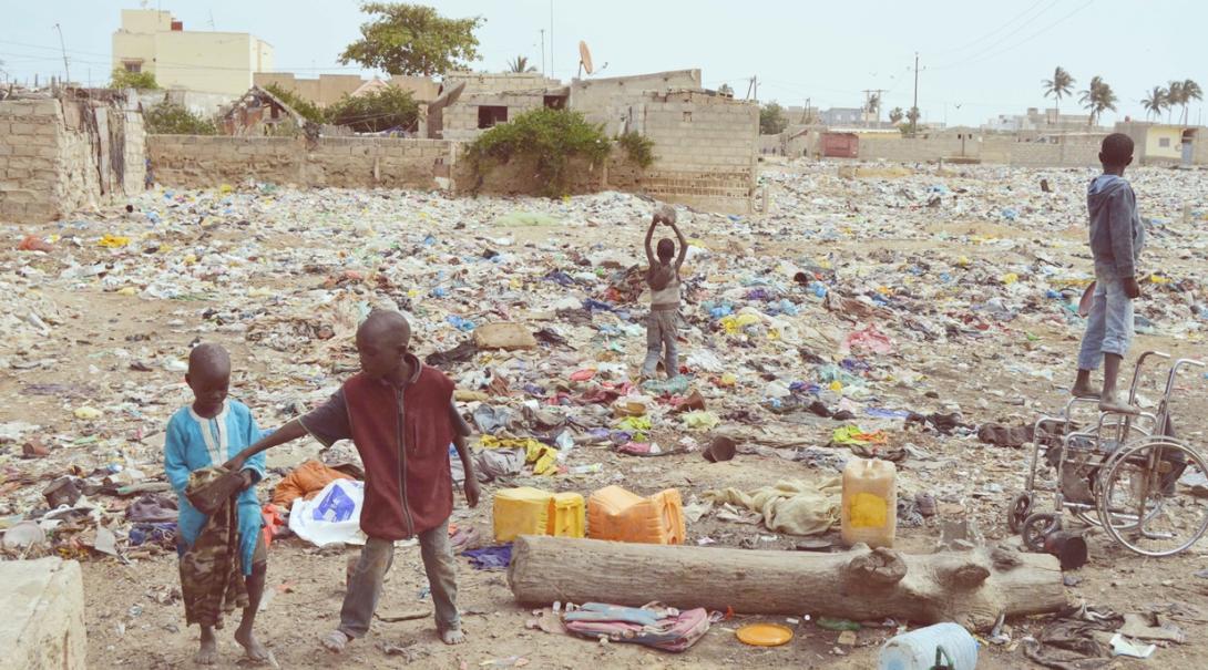 セネガルのゴミだらけの街角で裸足で遊ぶ幼い子供たち